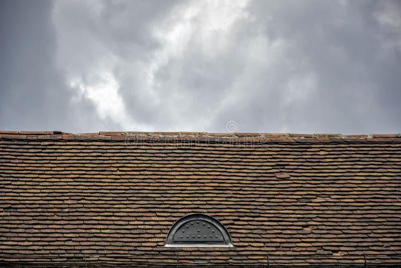 由赤土陶器瓦片做的减少老屋顶反对多云天空背景,一个老大厦的建筑细节 免版税库存照片