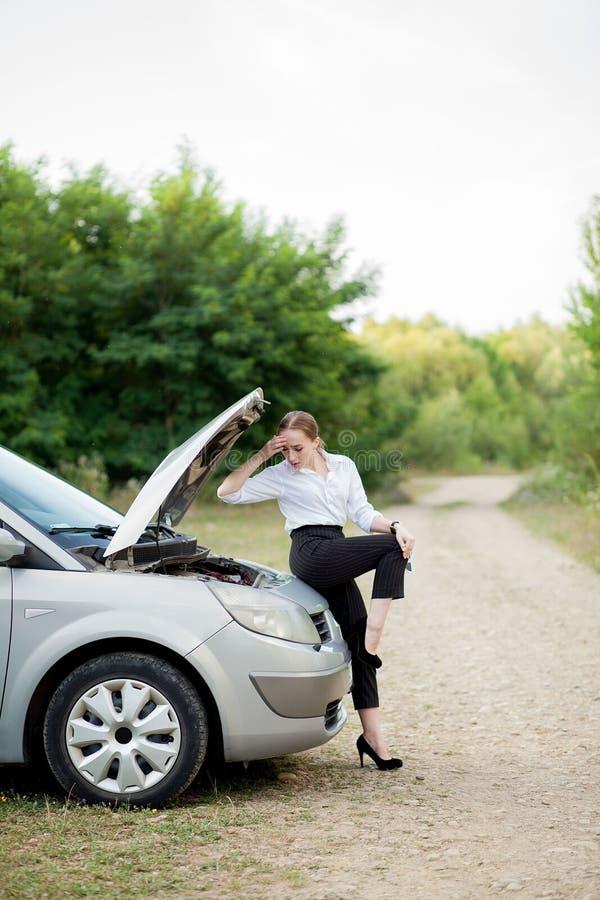 由路旁的年轻女人,在她的汽车有发生故障她后打开敞篷看损伤 免版税库存图片