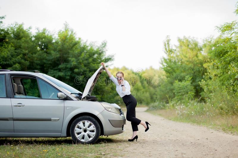 由路旁的年轻女人,在她的汽车有发生故障她后打开敞篷看损伤 图库摄影