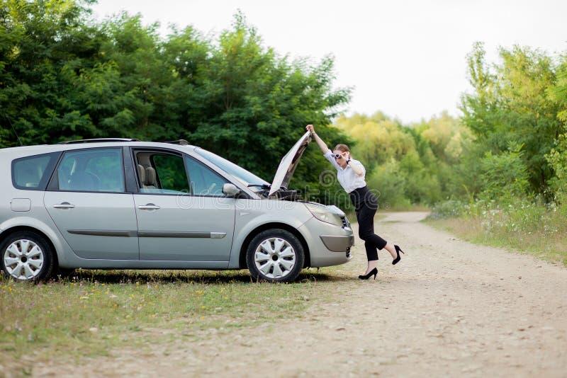 由路旁的年轻女人,在她的汽车有发生故障她后打开敞篷看损伤 免版税图库摄影