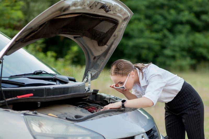 由路旁的年轻女人,在她的汽车有发生故障她后打开敞篷看损伤 免版税库存照片