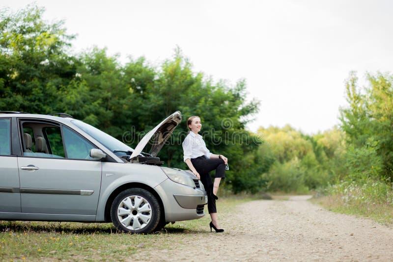 由路旁的年轻女人,在她的汽车有发生故障她后打开敞篷看损伤 库存图片