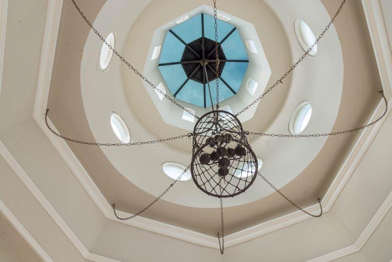 由金属做的黑枝形吊灯垂悬从白色八角形物圆顶 库存图片