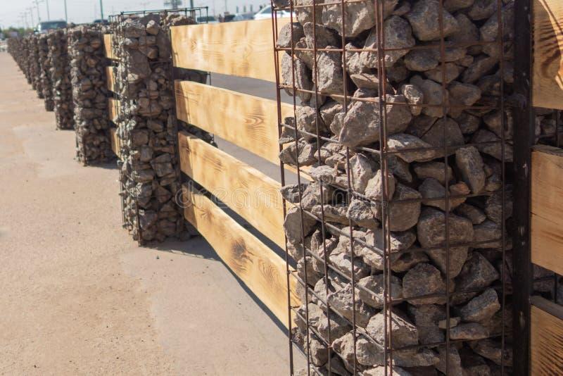 由金属房屋板壁做的现代篱芭和外形覆盖象作为木篱芭由有石柱子的水平的委员会做成 pilla 免版税库存照片