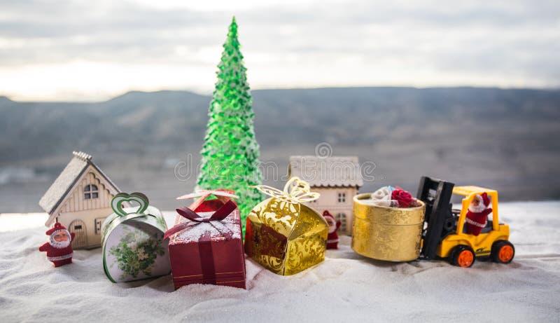 由铲车机器的微型礼物盒在雪,坚定的图象为圣诞节假日和新年快乐礼物庆祝概念 免版税图库摄影