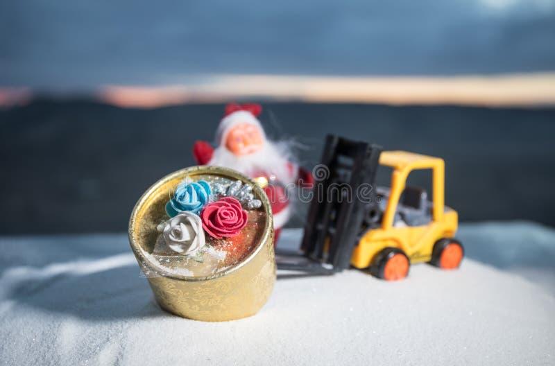 由铲车机器的微型礼物盒在雪,坚定的图象为圣诞节假日和新年快乐礼物庆祝概念 库存照片