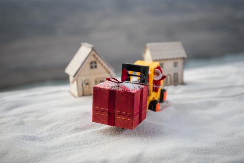 由铲车机器的微型礼物盒在雪,坚定的图象为圣诞节假日和新年快乐礼物庆祝概念 库存图片
