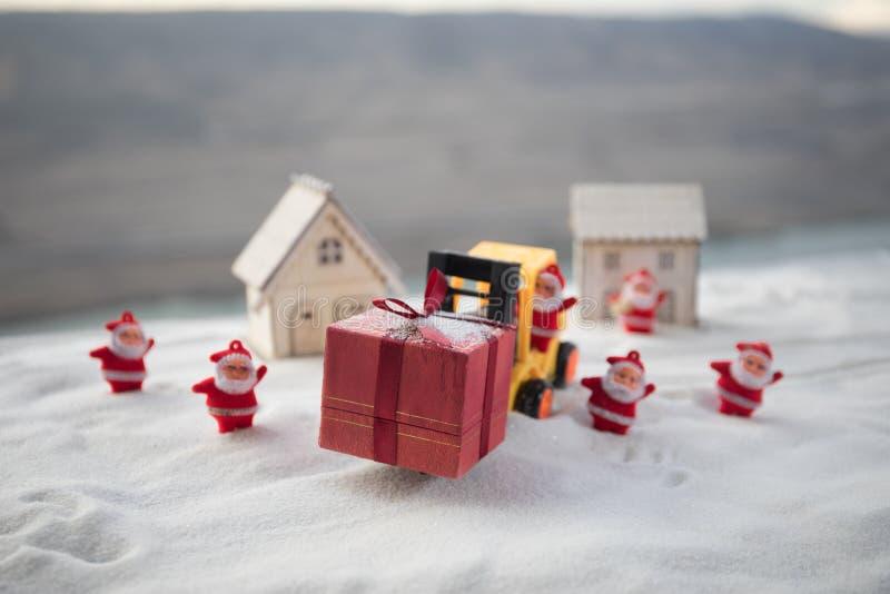 由铲车机器的微型礼物盒在雪,坚定的图象为圣诞节假日和新年快乐礼物庆祝概念 免版税库存照片