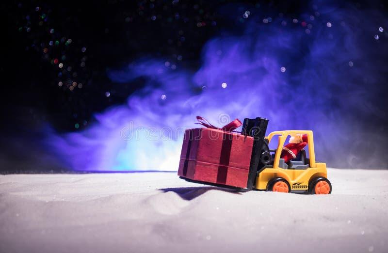 由铲车机器的微型礼物盒在雪,坚定的图象为圣诞节假日和新年快乐礼物庆祝概念 免版税库存图片