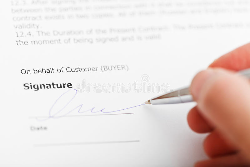 由银色笔的买家签署的销售合约 库存图片