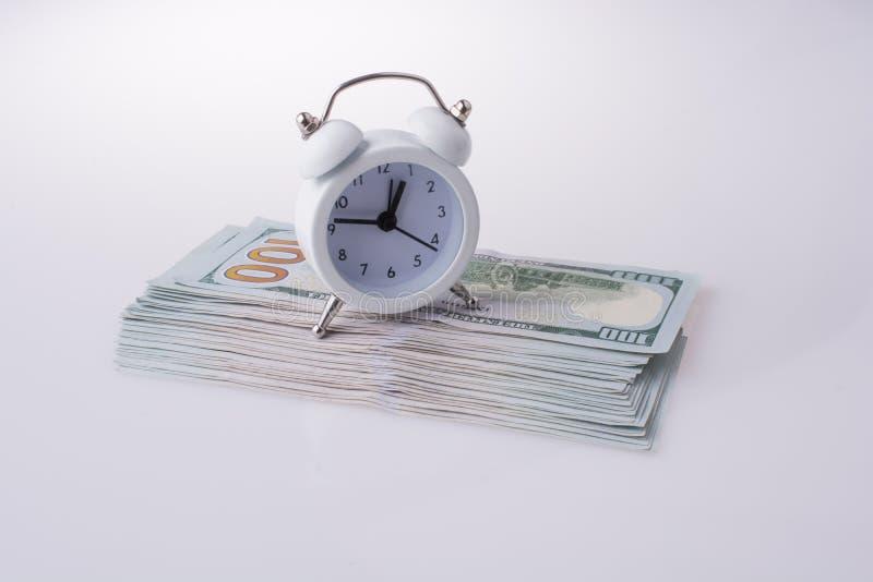 由闹钟的边的美国美元钞票 免版税库存图片