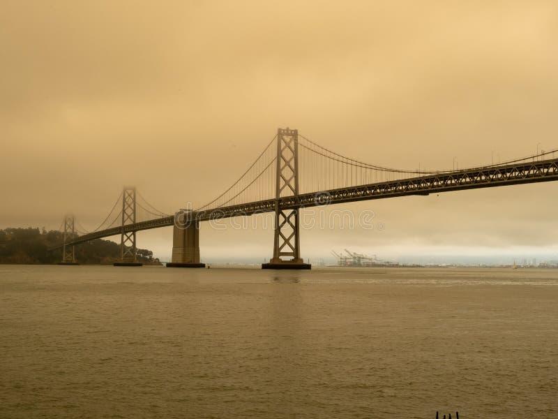 由附近的野火的烟雾围拢的海湾桥梁 新鲜空气在奥克兰港的距离能被看见  免版税库存照片