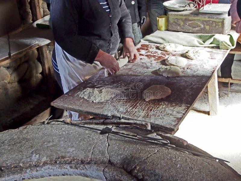 由面团的妇女的准备烘烤的格鲁吉亚面包的 免版税库存照片