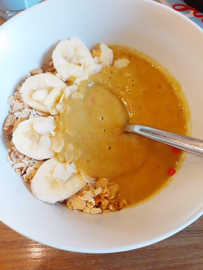 由香蕉和芒果做的健康食品圆滑的人与自创格兰诺拉麦片在一个白色碗特写镜头在浅褐色的背景 免版税图库摄影