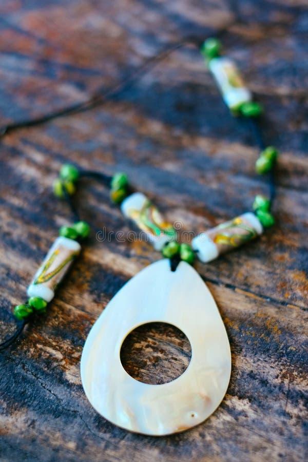 由鲍鱼壳和珊瑚小珠做的手工制造美丽的项链 免版税库存照片