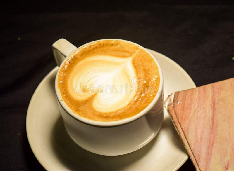 由Facebook dev app的自由基本在智能手机屏幕上 爱咖啡,拿铁艺术A杯子与心脏样式的在一个白色杯子 室内咖啡馆 图库摄影