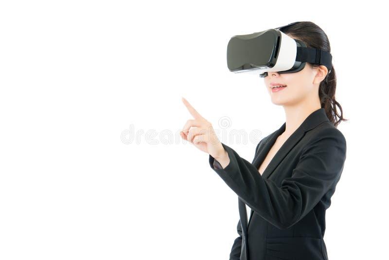 由VR耳机玻璃的亚洲女商人点屏幕 库存图片