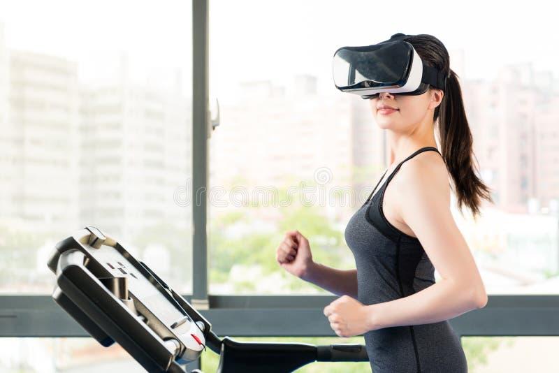 由VR耳机玻璃的秀丽亚裔妇女连续踏车 图库摄影
