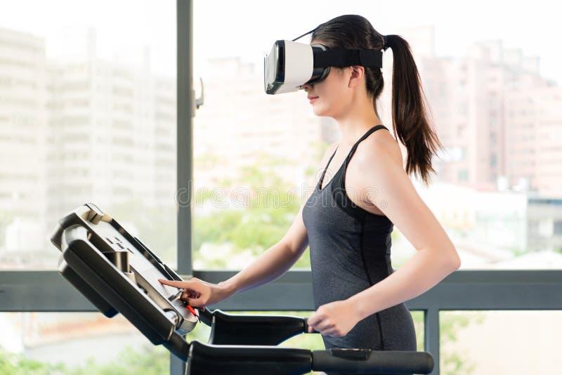 由VR耳机玻璃的秀丽亚裔妇女连续踏车 免版税图库摄影