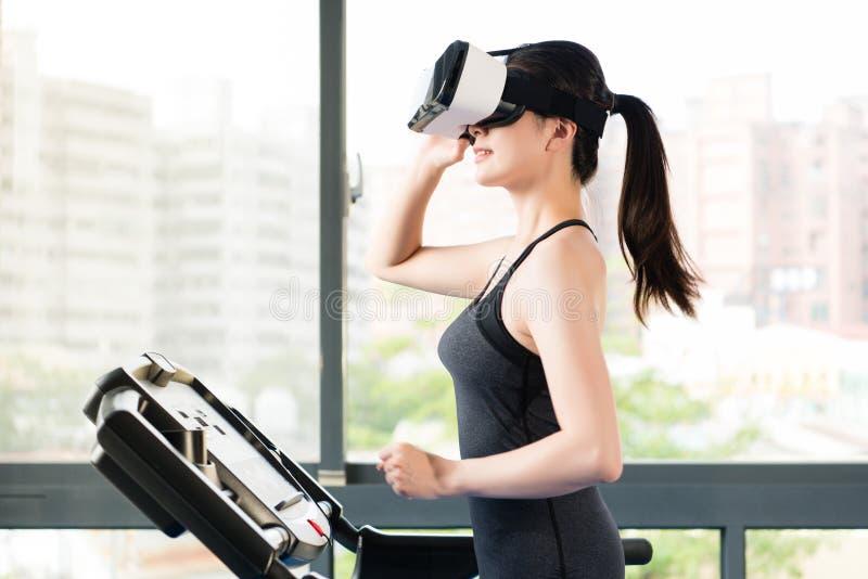 由VR耳机玻璃的秀丽亚裔妇女连续踏车 库存照片