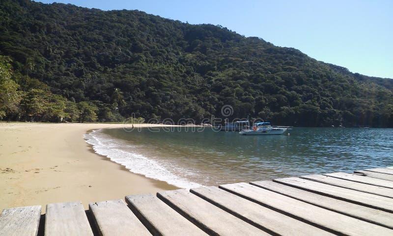 甲板木头、小船和海滩 库存图片
