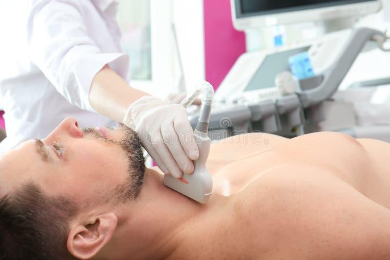 甲状腺的医生举办的超声波考试 免版税图库摄影