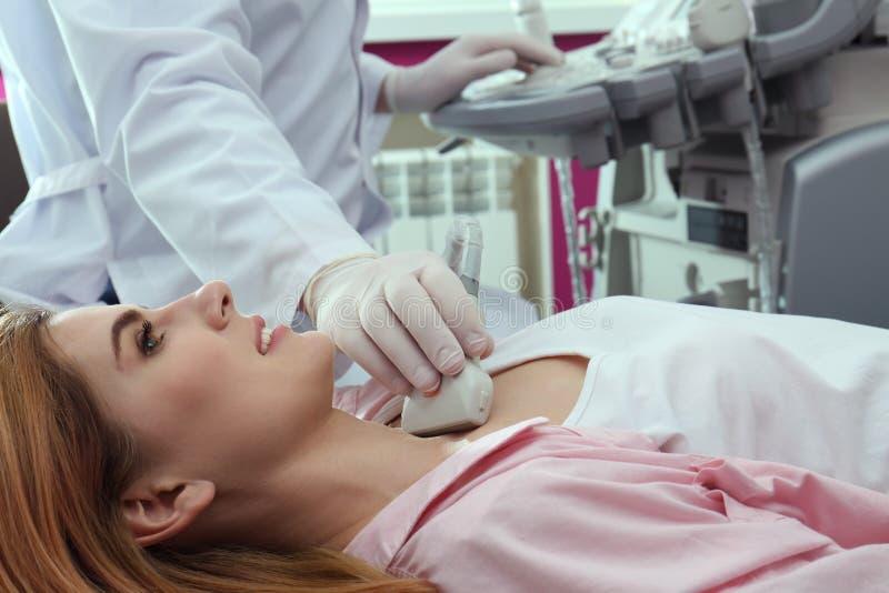 甲状腺的医生举办的超声波考试 免版税库存照片