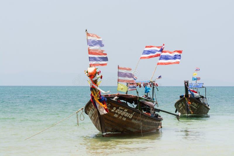 甲米府,泰国- 2019年3月:有泰国旗子的长尾巴木小船被停泊在Railay海滩 免版税库存照片