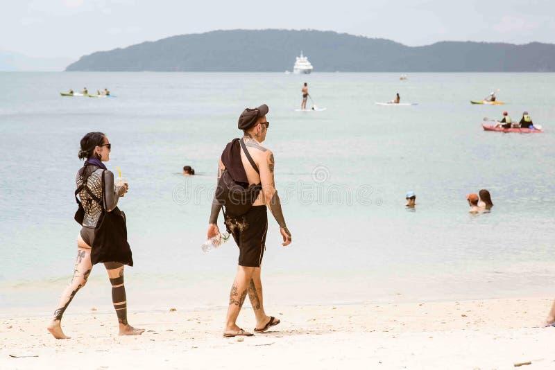 甲米府,泰国- 2019年2月12日:用纹身花刺和女孩沉重盖的人在一个热带沙滩走 刺字 免版税库存照片