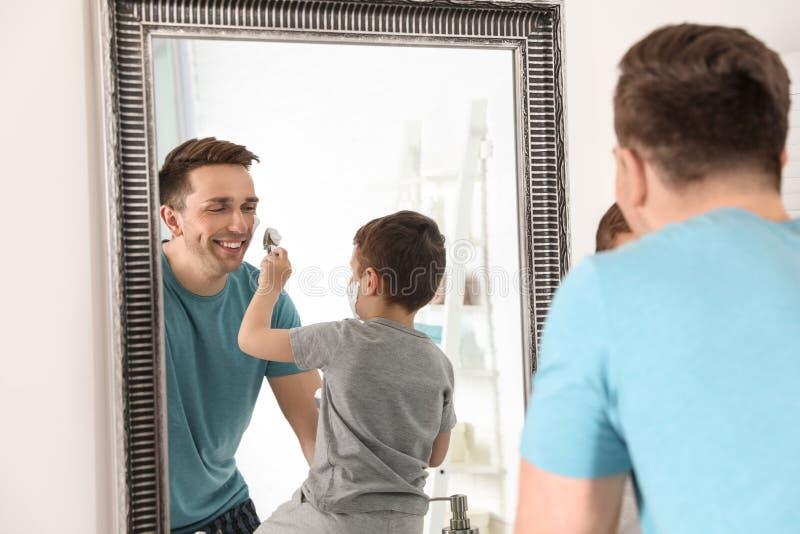 申请一点的儿子刮在爸爸的面孔上的泡沫 免版税库存照片