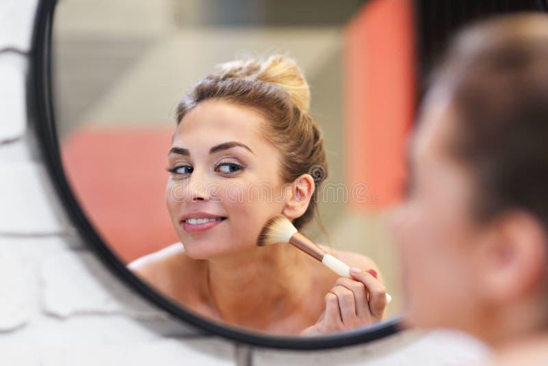 申请与刷子的年轻女人构成在卫生间里 库存图片