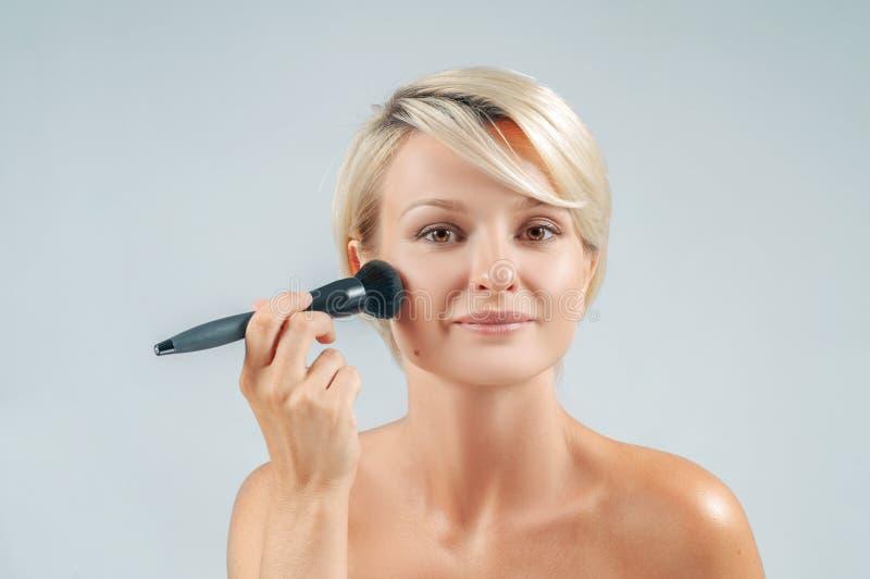 申请与粉末刷子的美女构成在看镜子的面孔 库存图片
