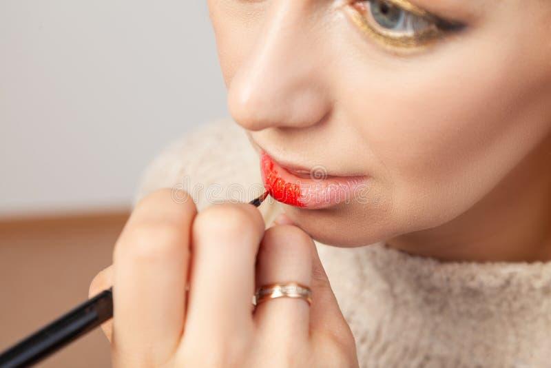 申请在嘴唇的特写镜头,化妆师在她的手上拿着一把刷子并且应用在模型的开放嘴的红色口红 库存照片