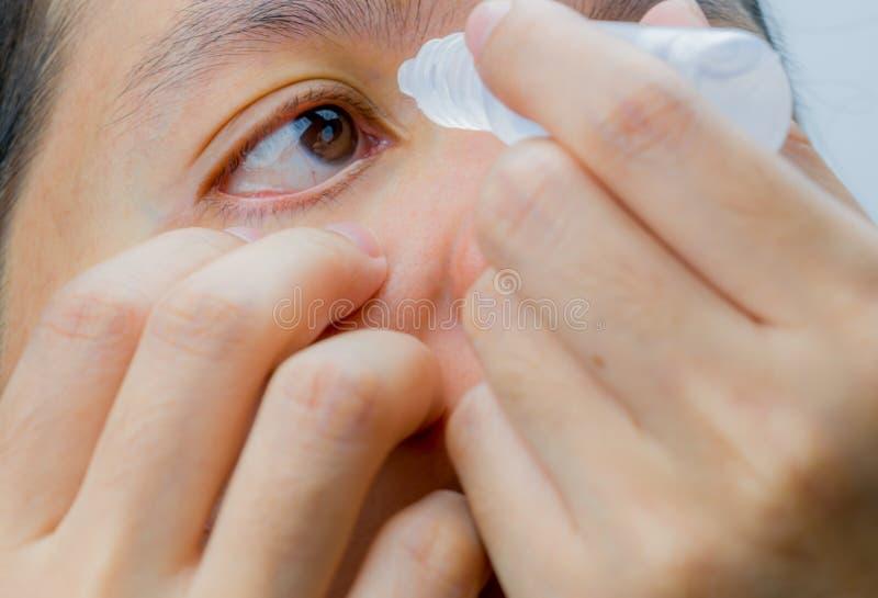 申请在她的棕色眼睛的成人亚裔妇女眼药水 眼睛关心 库存照片