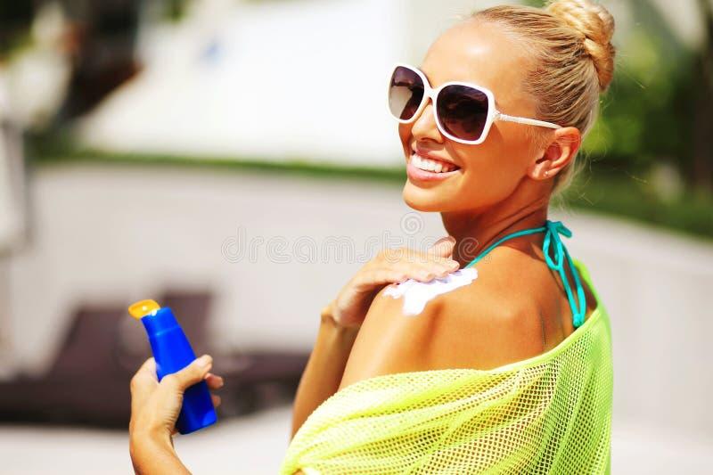 申请在她的肩膀的妇女遮光剂保护 免版税库存图片