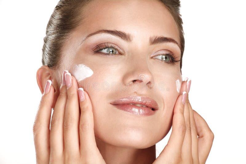 申请在她的面孔的美好的模型化妆奶油色treatmen 库存照片