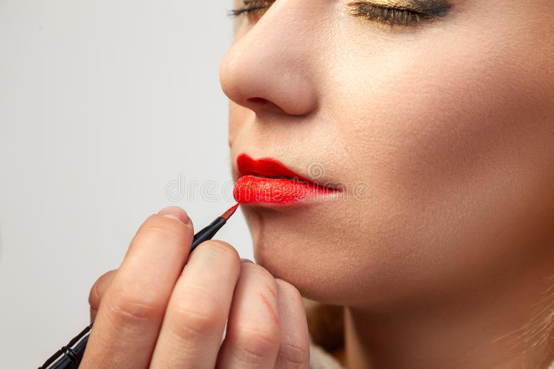 申请在模型的嘴唇的构成特写镜头,化妆师在她的手上拿着一把刷子并且应用红色口红, 库存照片
