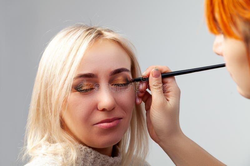 申请在沙龙的构成特写镜头在东方样式的模型,投入金黄棕色树荫的化妆师和 免版税图库摄影