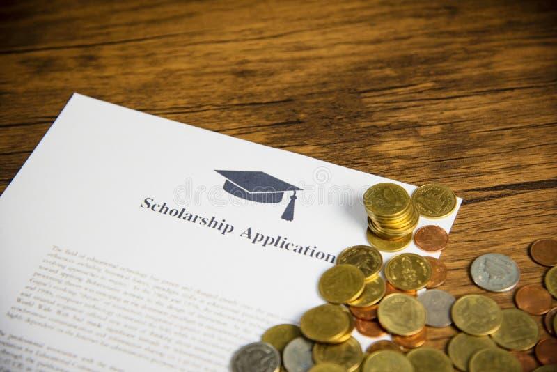 申请奖学金文件合同与金钱硬币的形式概念津贴在木桌上的奖学金教育的 库存图片