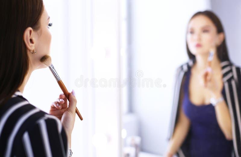 申请她的构成的年轻美女的反射,看在镜子 免版税库存照片