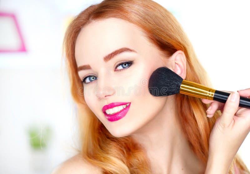 申请构成的秀丽妇女 看在镜子和应用化妆用品的美丽的女孩 库存照片