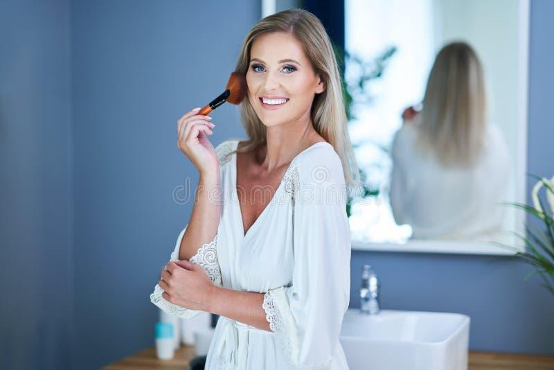 申请构成的美丽的深色的妇女在卫生间里 库存图片