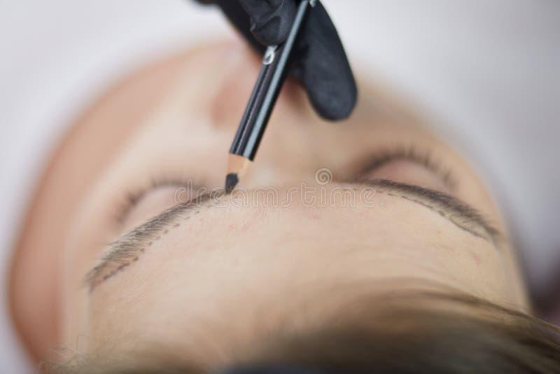 申请永久的美容师在眼眉组成 库存照片