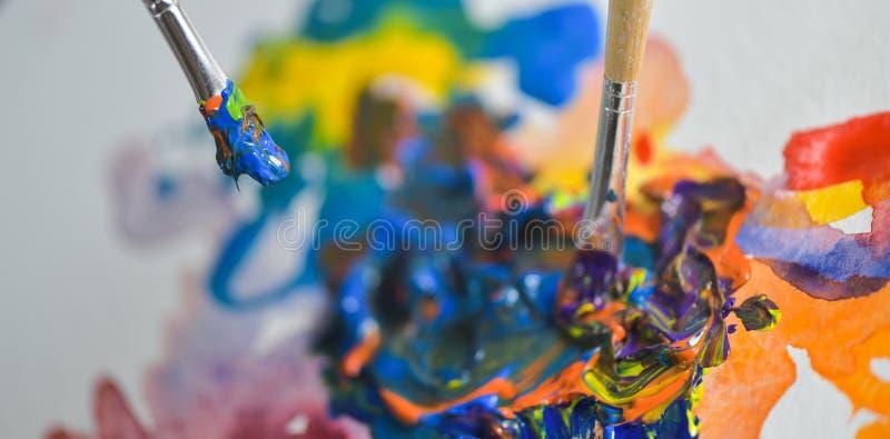 申请油漆树胶水彩画颜料的艺术家的手 库存图片