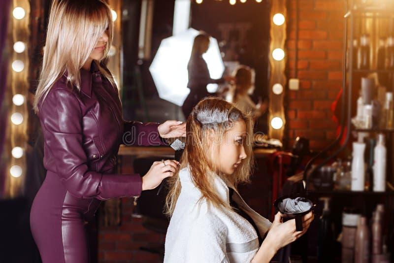 申请颜色的专业女性美发师于女性顾客在美发店 理发服务,头发恢复产品, 库存图片