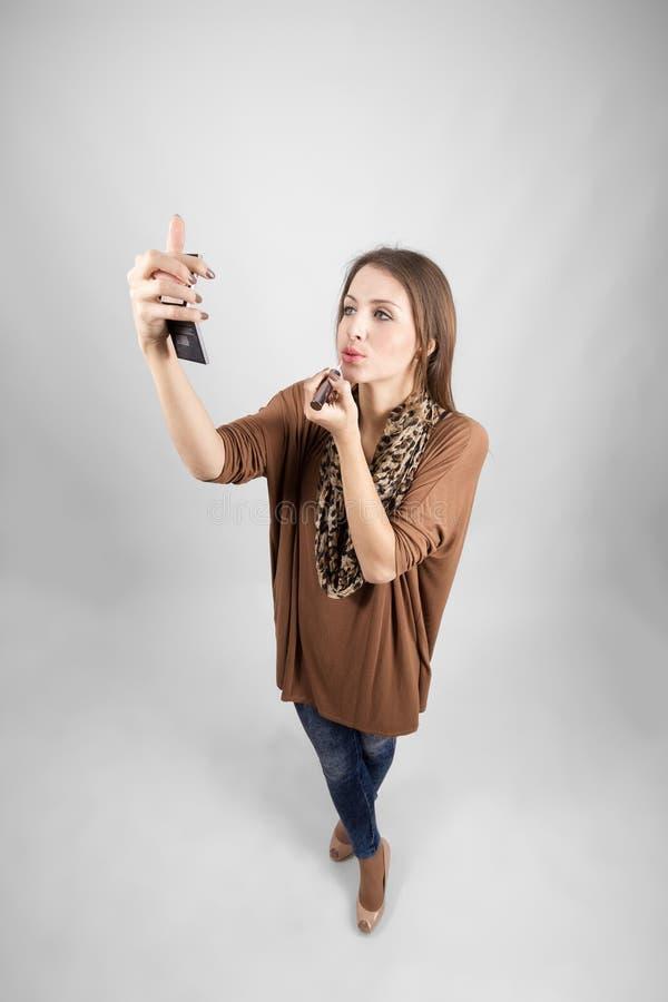 申请嘴唇光泽的年轻美好的时装模特儿 免版税图库摄影