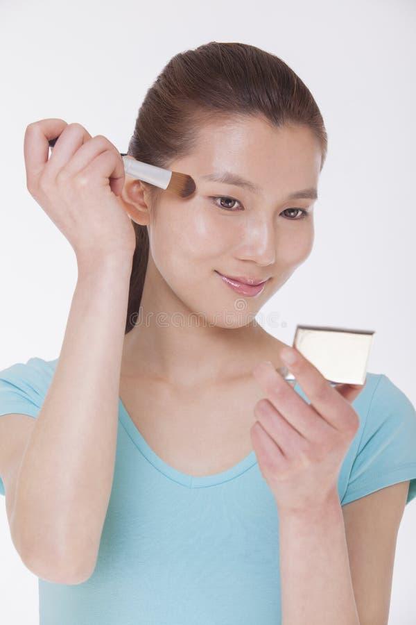 申请年轻美丽的妇女调查镜子和用制造刷子,演播室射击组成 免版税库存照片
