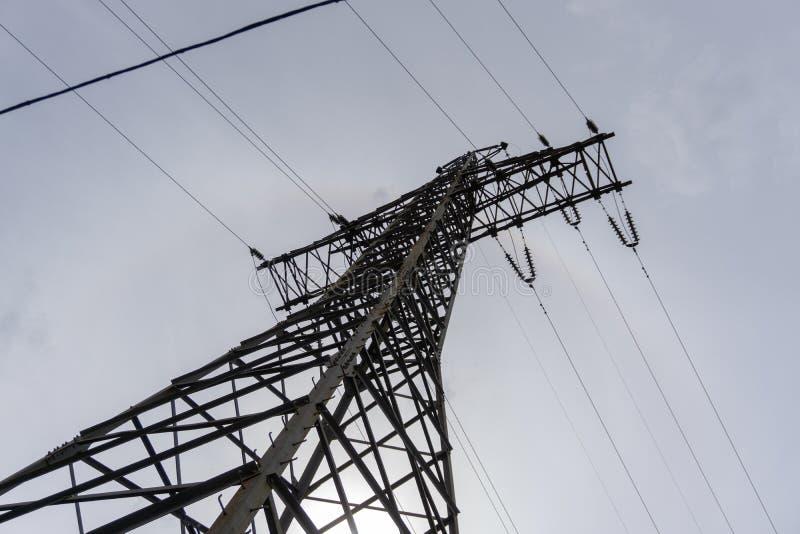 电传输定向塔现出轮廓反对灰色天空在黄昏 免版税库存照片