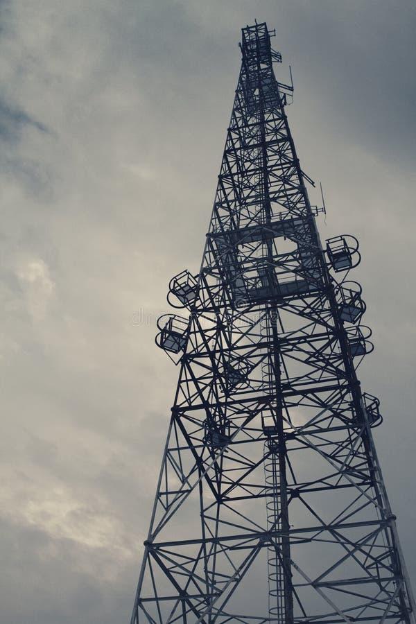 电信塔成为了剪影线从在暮色时间的白色天空引人注意 免版税库存照片