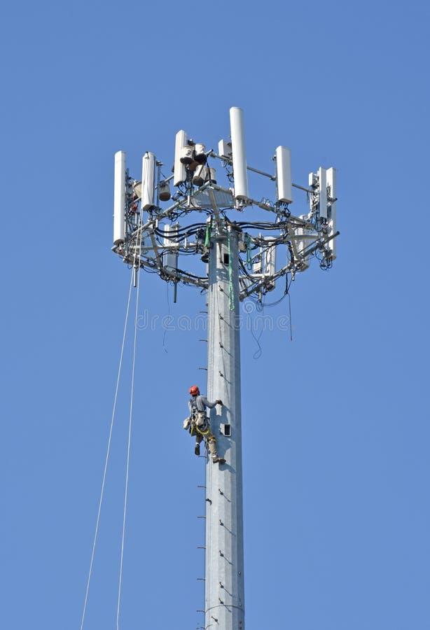 电信工作者攀登细胞塔 免版税库存照片